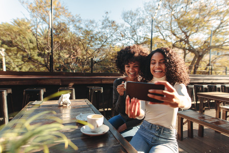 Two young women clicking selfie using a mobile phone at a coffee shop. Friends sitting with coffee cups on table having fun with a smart phone.