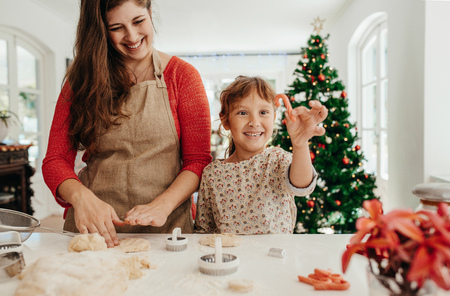 mother and daughter making christmas cookies using dough moulds and cutters little girl holding candy - Making Christmas Cookies