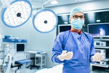 멀리 찾고 작업 극장에서 수술 유니폼에 여성 외과 의사의 초상화. 수술 용 및 현대 병원 운영 방에 의료 마스크 의사.