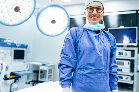 Portrait of smiling female surgeon in surgical uniform at operating room. Young woman doctor in hospital operation theater.