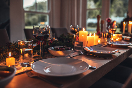 Close up shot of christmas festive table with no people. Dining table with plates, wine glasses and candles. Archivio Fotografico