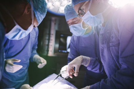 Female surgeon with her team performing surgery on patient in hospital operating room. Medics during surgery in operation theater. Stock Photo
