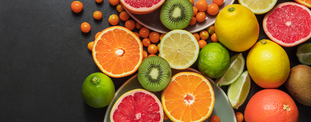 Variety of fruits in serving plates and on table. Grapefruit, oranges, lime, kiwi fruit and sea berries bunched together on a table.