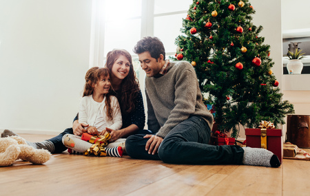 Family sitting beside Christmas tree opening gifts. Small family having happy time together on Christmas. Stok Fotoğraf