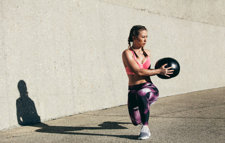 Sportswoman doing stretching exercise with medicine ball. Muscular woman exercising fitness ball outdoors. Stock Photo
