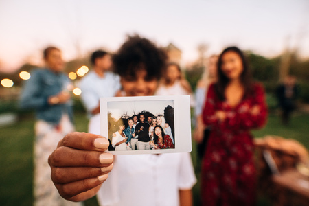 Woman showing picture in front with friends partying in background. Group photo of party people. Stock Photo