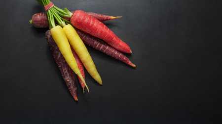 Colorful carrots and radishes bunched together on table with black background.