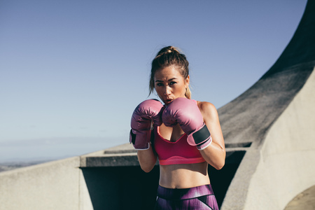 Healthy young woman wearing boxing gloves in combat stance. Fit young female boxer ready for fight outdoors.