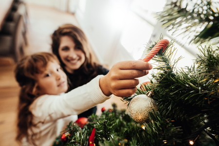 Mother and daughter placing candy cane on Christmas tree. Young woman helping her daughter decorate Christmas tree.