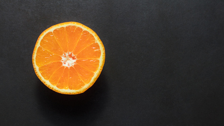 Top view of a half cut orange placed on a black background.