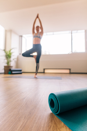 Close up of yoga mat in fitness center and blurred woman at the back in tree yoga pose. Fitness mat on floor with woman practising yoga in background.