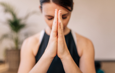 Close up of woman hands joined. Female meditating with her hands joined indoors. Namaste yoga pose, meditating, breathing and relaxing.