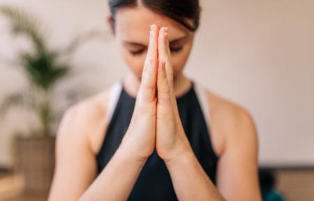 Schließen Sie oben von den verbundenen Frauenhänden. Die Frau, die mit ihren Händen meditiert, schloss sich zuhause an. Namaste Yoga-Pose, meditieren, atmen und entspannen. Standard-Bild