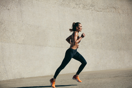 Healthy young woman running in morning. Fitness model exercising in morning outdoors. Full length side view shot.