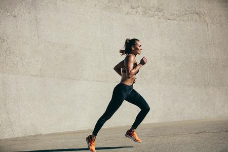 Mujer joven sana corriendo en la mañana. Modelo de fitness ejercicio en la mañana al aire libre. Tiro de vista lateral de longitud completa. Foto de archivo