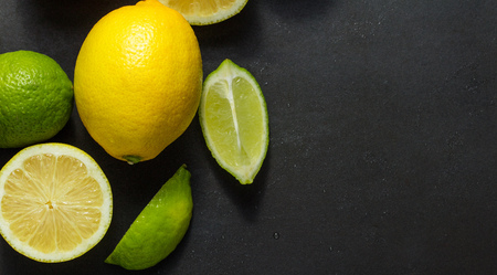 Cut and uncut limes and lemons on a black background. Top view of limes and lemons on table. 版權商用圖片