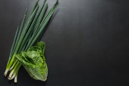 Bunch of green spring onions or scallions and napa cabbage on a black background.