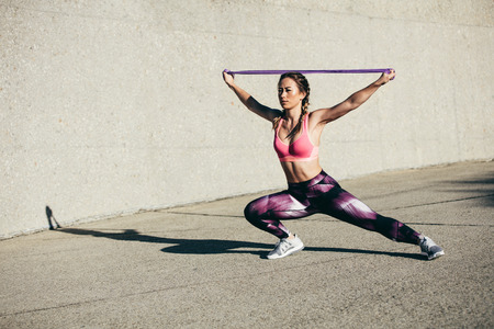 Strong young woman stretching with resistance band. Fitness female athlete exercising outdoors.