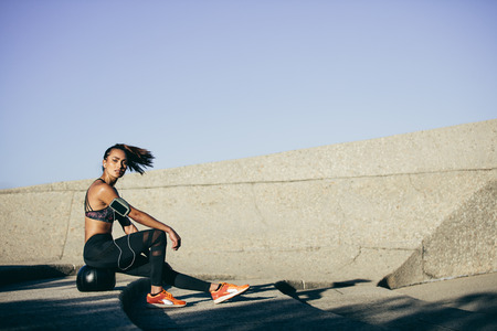 Fitness woman sitting on a exercise ball after workout. Female taking a rest after training session outdoors.