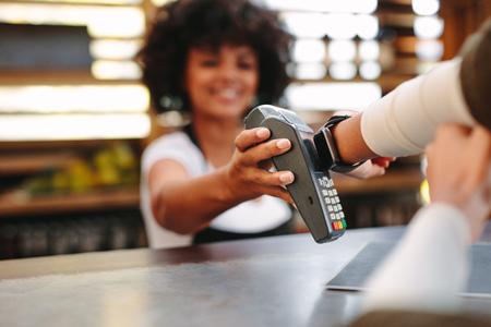 Klant die draadloze of contactloze betaling doet met smartwatch. Kassier die betaling over nfc-technologie accepteert. Stockfoto