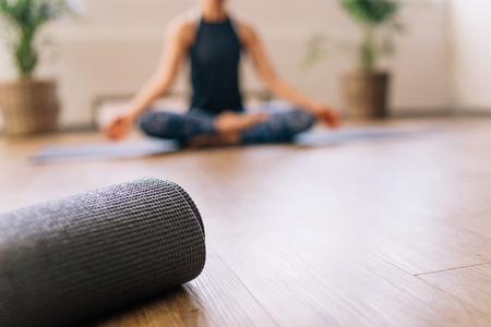 Close-up van gerolde yoga mat in fitnesscentrum en wazige vrouw aan de achterzijde in lotus yoga pose. Fitness mat op de vloer met een vrouw yoga op de achtergrond.