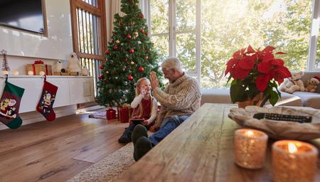 クリスマス期間中に自宅の小さな女の子と中年の男性の屋内撮影。成熟した男は床に座って彼の孫娘にハイファイブを与えます。 写真素材 - 87606761
