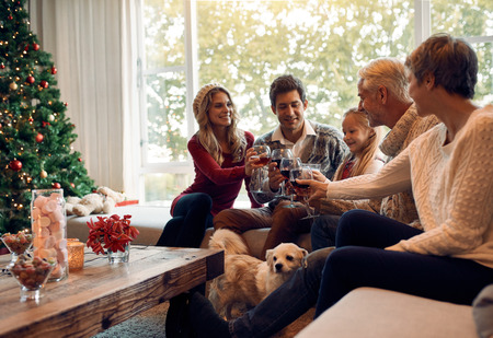 tradition: Happy family toasting with wine on Christmas eve. Family gathering at home for christmas festival, celebrating with wine.