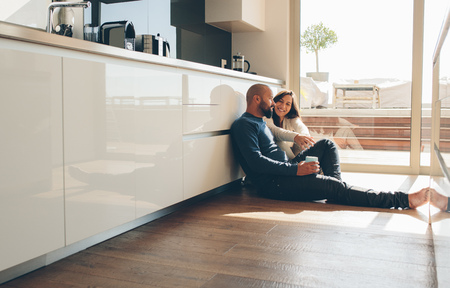 Young man and woman sitting on floor in kitchen and talking. Loving young couple spending time together at home. Stok Fotoğraf