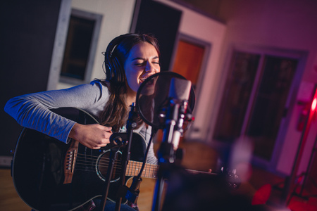 Female vocal artist singing in a recording studio with guitar. Woman singer singing a song and playing guitar.