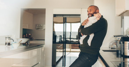Happy young man carrying his newborn baby boy in arms in kitchen. Happy father with son sleeping in his arms in kitchen. 版權商用圖片