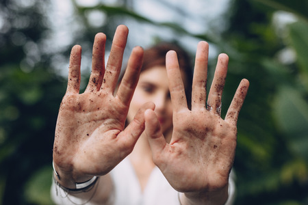 Close up of female gardener showing her dirty hands with soil and earth at greenhouse. Woman after garden work and landscaping in the plant nursery. Stock Photo