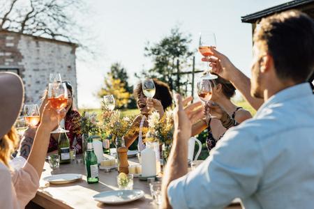 Vrienden die dranken roosteren op een feestje. Jongeren die in openlucht restaurant hangen en van dranken genieten.