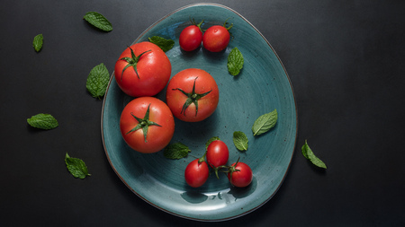Ripe tomatoes and mint leaves in a plate. Big and small sized tomatoes in a ceramic plate on black  background.