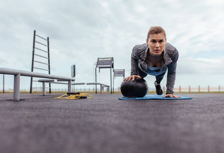 Young and fit sportswoman doing pushups in outdoor gym. Fitness woman doing push-ups with exercise ball. Stock fotó