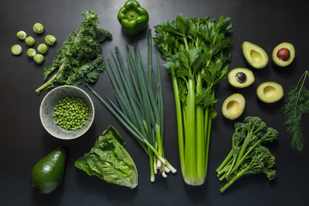 Vegetables arranged on table. Bunch of scallions, avocados, celery, peas, brussel sprouts,  capsicum on black background. Stock Photo