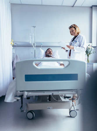 Smiling doctor with clipboard visiting man at hospital ward. Physician attending patient in hospital bed and looking at reports. Stock fotó