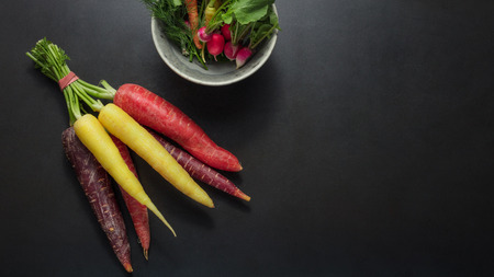 Colorful carrots and radishes bunched together on table alongside a bowl dill leaves, spinach and radishes. 版權商用圖片