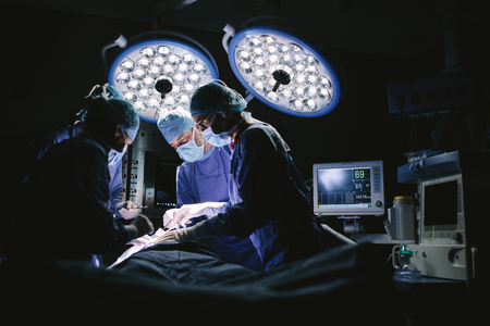 Team of surgeons doing surgery in hospital operating room. Medical team doing critical operation.