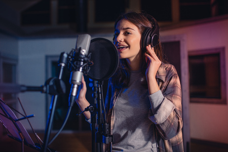 Young female singer recording album in the professional studio. Woman singing a song in music recording studio.