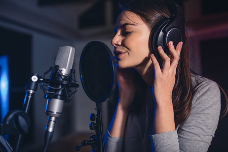 Close up of female vocal artist singing in a recording studio. Woman playback singer singing a song.