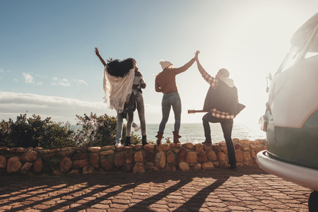 Friends on road trip standing on embankment along the road . Group of young people on holiday having fun outdoors. Stock Photo