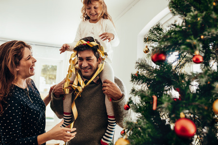 Happy young couple with their daughter celebrating Christmas. Little girl sitting on her father's shoulders and having fun. Standard-Bild
