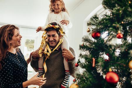 Szczęśliwa młoda para z córką obchodzi Boże Narodzenie. Mała dziewczynka siedzi na ramionach ojca i bawi się.