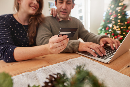 Man using laptop and woman holding credit card. Young couple shopping online with credit card at home for Christmas, focus on credit card. Stock Photo