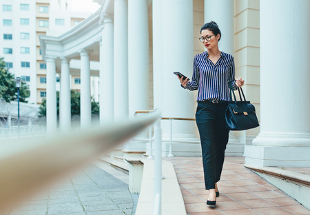 Outdoor shot of young woman using mobile phone outdoors in the city. Female business professional using smart phone in the city. Reklamní fotografie