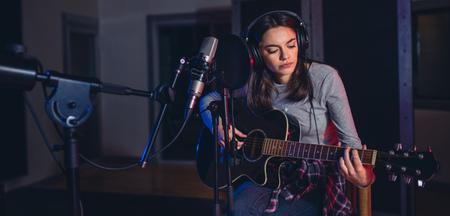 Feminino cantor interpretando uma música em estúdio e tocando violão. Artista vocal de mulher tocando violão em um estúdio de gravação. Foto de archivo - 88435578