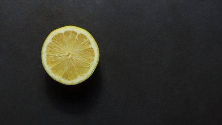Top view of a half cut lemon placed on a black background. Reklamní fotografie