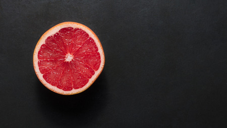 Top view of a half cut grapefruit placed on a black background. Orange with red pulpy centre. Stock Photo