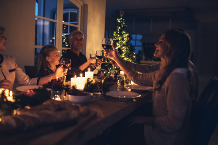 Happy family toasting wine glasses at dining table in the house. Family at dining table for christmas dinner in the house.