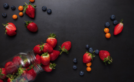 Fresh strawberries and blueberries on black background. Strawberries falling out of a glass jar. Stock Photo
